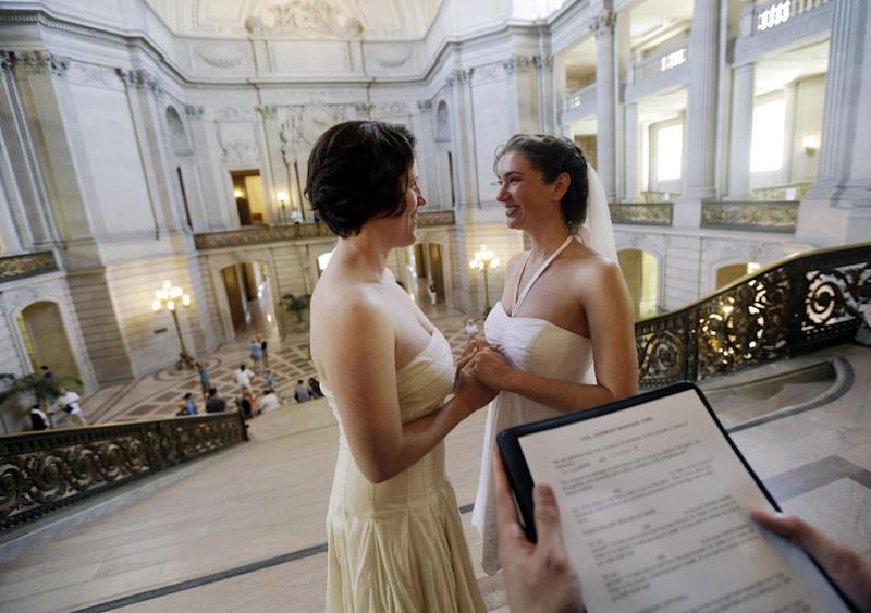 Cynthia Wides, right, and Elizabeth Carey exchange wedding vows at City Hall in San Francisco, Saturday, June 29, 2013. Dozens of gay couples have lined up outside City Hall in San Francisco as clerks have resumed issuing same-sex marriage licenses one day after a federal appeals court cleared the way for the state of California to immediately lift a 4-year freeze. (AP Photo/Marcio Jose Sanchez)