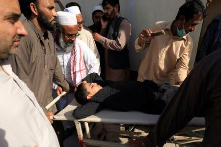 People move a child on stretcher after what they say was a defective vaccine administered outside a hospital in Peshawar,