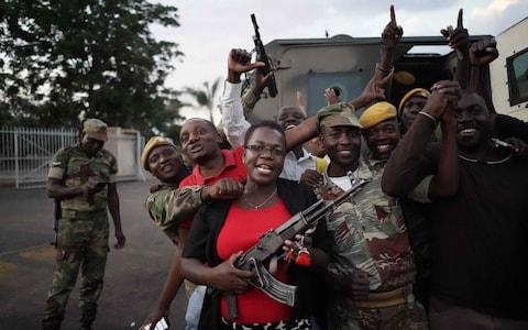 People and soldiers celebrate after the resignation of Zimbabwe's president on November 21, in Harare - Credit: MARCO LONGARI/AFP