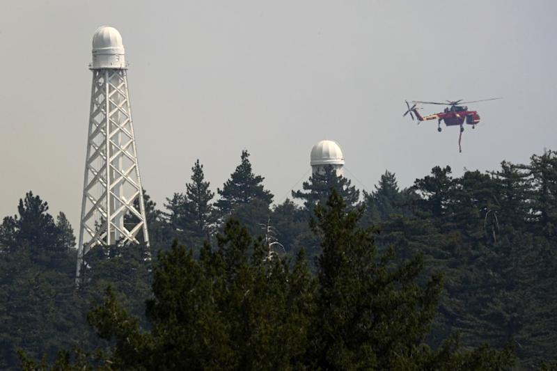 A helicopter fights the Bobcat fire burning dangerously close to Mt. Wilson Observatory.