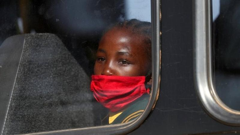 A girl wearing a mask looks on through a bus window in Eikenhof, south of Johannesburg, South Africa. Photo: August 2020