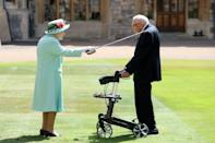 Britain's Queen Elizabeth II uses the sword that belonged to her father, George VI as she confers the Honour of Knighthood on 100-year-old veteran Captain Tom Moore at Windsor Castle in July 2020