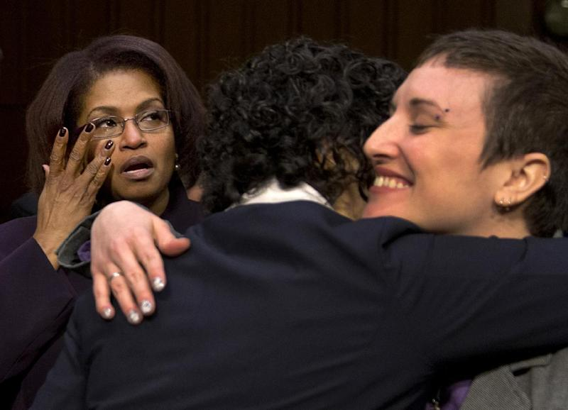 Former US Army Specialist BriGette McCoy, left, wipes a tear as former US Army Sgt. Rebekah Havrilla, right, hugs Anu Bhagwati, a former Marine officer and Executive Director and Co-Founder of Service Women's Action Network, after they all testified on Capitol Hill in Washington, Wednesday, March 13, 2013, before the Senate subcommittee on Personnel hearing on sexual assault in the military. (AP Photo/Carolyn Kaster)