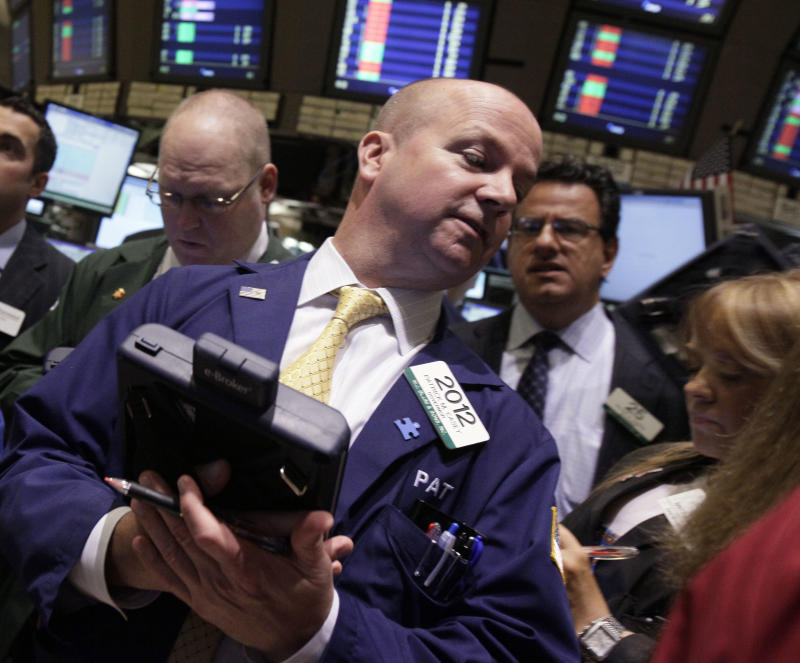 In a Monday, May 7, 2012, photo, trader Patrick Casey, center, works on the floor of the New York Stock Exchange.   Futures pointed to losses on Wall Street with Dow Jones industrial futures  and S&P 500 futures down 0.5 percent.   (AP Photo/Richard Drew)