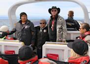 <p>As the boat kept moving along the coast and found calmer waters near a section of land, Joan Morris and Garry told us stories from the Songhees Nation about their history and their lands. A section of land near a hotel used to be where Elder Joan Morris' family lived and foraged for food. Near Turkey Head Point there was a village site 200-300 years ago. Over here in this small bay, at night during the winter months, nation members walk out onto wet mud during low tide to harvest clams. <em>Why only in winter?</em> In the summer months the clams are too exposed and build up toxins (which make them uneatable). The most peaceful moment of the trip was when Garry, in his softly spoken voice, sang the song of the warriors. Pictured here: Garry (left), Joan Morris (middle) and Mark Salter (right). [Photo credit: Eagle Wing Whale & Wildlife Tours] </p>