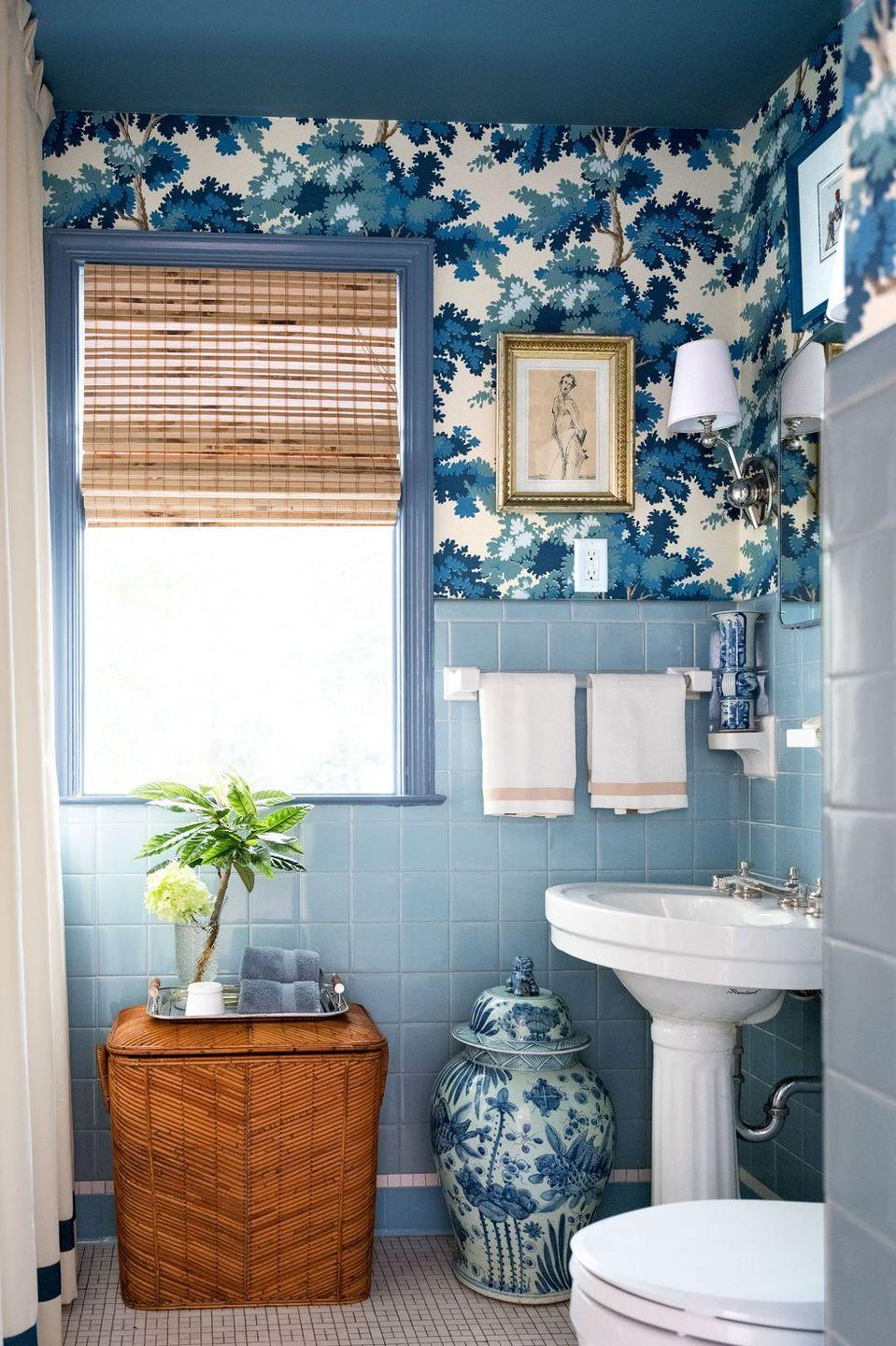"""<p>Don't let tiny rooms deter you from going big. Interior designer <a href=""""http://shaunsmithhome.com/"""" rel=""""nofollow noopener"""" target=""""_blank"""" data-ylk=""""slk:Shaun Smith's"""" class=""""link rapid-noclick-resp"""">Shaun Smith's</a> New Orleans home is a treasure trove of beautiful and clever design solutions. If your bathroom is too small for shelves with a lot of depth, add extra storage by placing a tray over the hamper. Keep your hand towels and florals there to brighten up the room. And most importantly, have fun with color.</p>"""