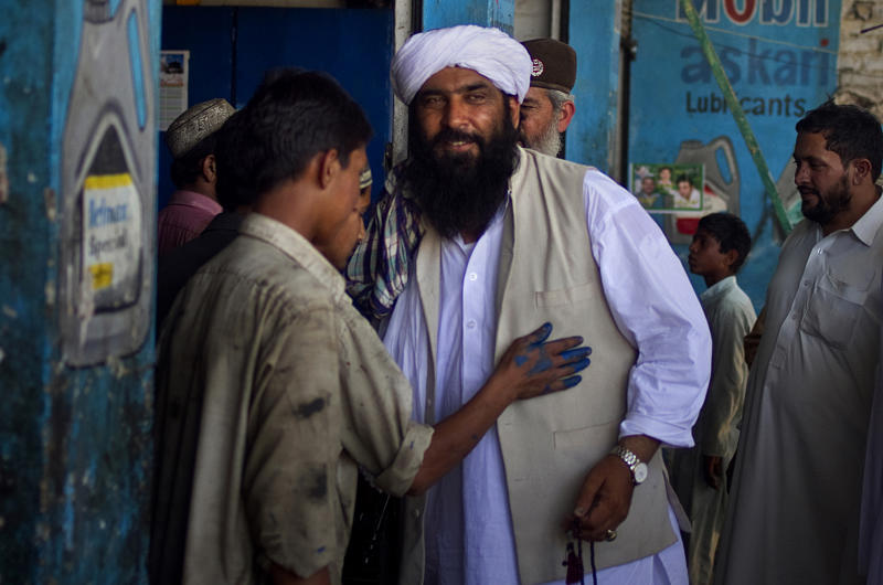 "In this Thursday, May 2, 2013 photo, Maulana Shujaul Mulk, center, pro-Taliban Jamiat-e-Ulema Islam (JUI-F), meets with workers during his election campaign at a market in Mardan, Pakistan. Mulk is among several Pakistani Islamists and sectarian groups contesting for the country's upcoming parliamentary elections, which are divided and scattered though, they are still in a position to secure enough strength to play Pakistani establishment bid to ""hound"" the next frail government in influencing its decisions about the U.S. forces withdrawal from Afghanistan in 2014. (AP Photo/Anjum Naveed)"