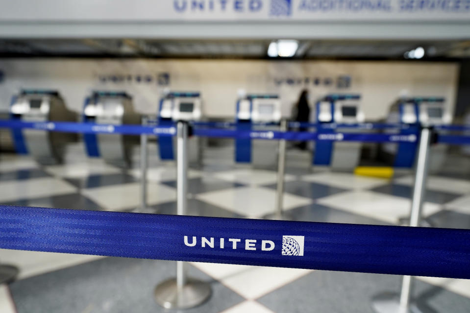 FILE - In this Oct. 14, 2020 file photo, empty ticketing counters are seen in Terminal 1 at O'Hare International Airport in Chicago. United Airlines says it could be using small electric-powered aircraft to take customers to the airport within a few years. United said Wednesday, Feb. 10, 2021, that it will buy up to 200 small aircraft capable of helicopter-style takeoffs and landings from startup Archer. (AP Photo/Nam Y. Huh, File)