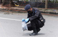 A member of the police bomb squad collects evidence from around the site of a bomb attack at the Sacred Heart of Jesus Cathedral in Makassar, South Sulawesi, Indonesia, Monday, March 29, 2021. Two attackers believed to be members of a militant network that pledged allegiance to the Islamic State group blew themselves up outside the packed Roman Catholic cathedral during a Palm Sunday Mass on Indonesia's Sulawesi island, wounding a number of people, police said. (AP Photo/Masyudi S. Firmansyah)