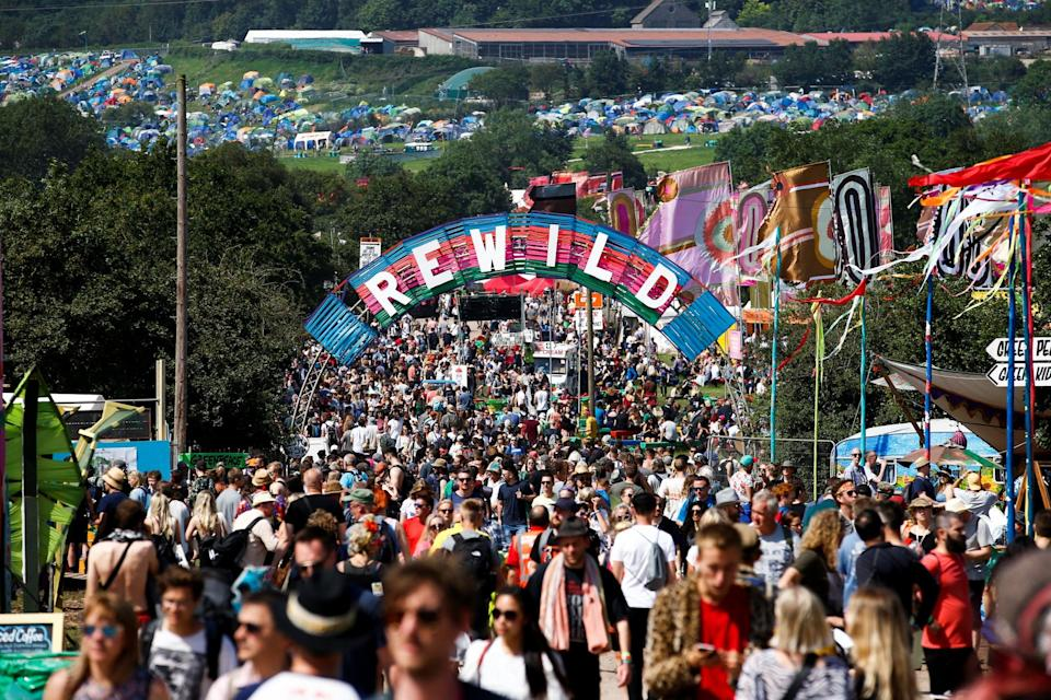 <p>Revellers walk along a track at the last Glastonbury Festival held in 2019</p> (Reuters)