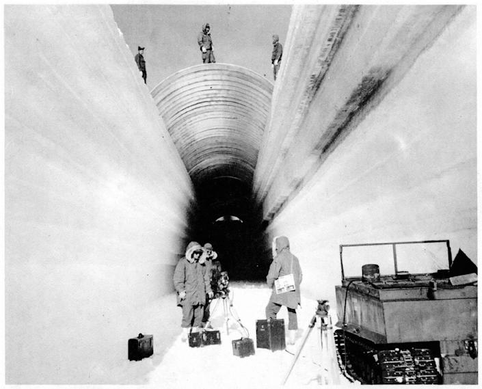 Workers cover a trench to build the under-ice military base
