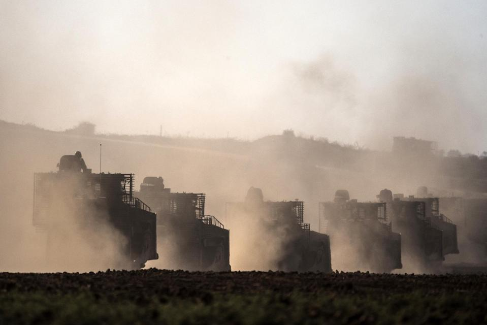 Israeli bulldozers roll along the southern border with the Gaza Strip following air strikes on July 10, 2014 (AFP Photo/Jack Guez)