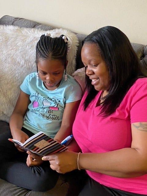 Nicole Johnson and her daughter Khloe look at their planner.