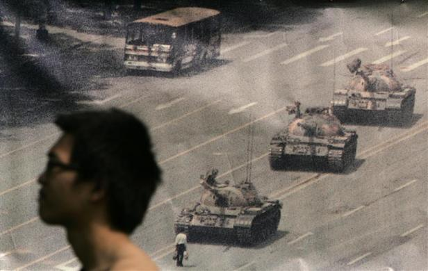 A man walks past a banner, printed with a photo of a man standing in front of tanks during the 1989 military crackdown on pro-democracy protesters around Beijing's Tiananmen Square, at Hong Kong's Victoria Park June 4, 2009.