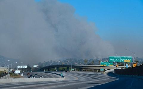 A huge plume of black smoke from Bel-Air rises east of the closed-off 405 freeway heading north  - Credit: AFP