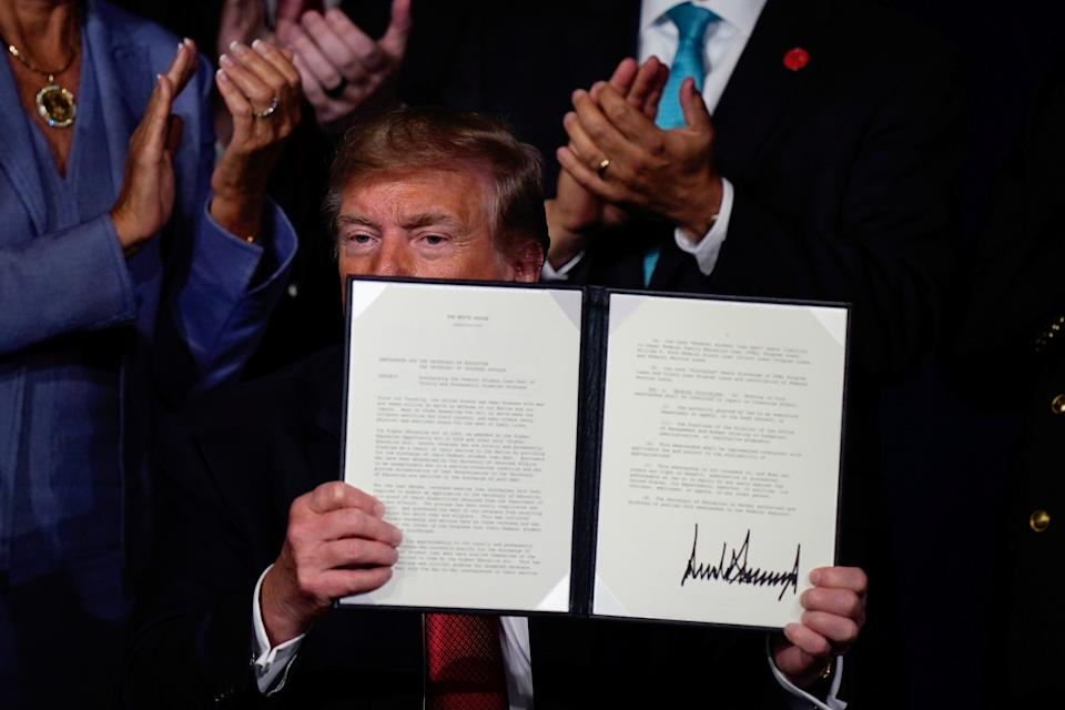 U.S. President Donald Trump holds an executive order relieving qualified disabled veterans of federally held student loan debt after speaking at the AMVETS (American Veterans) National Convention in Louisville, Kentucky. U.S., August 21, 2019.   REUTERS/Bryan Woolston