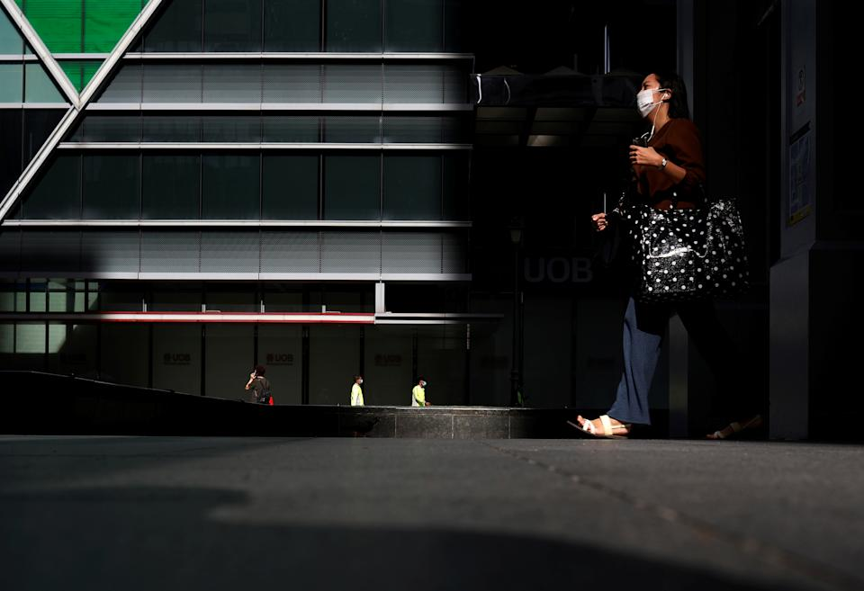 Office workers are seen at a largely empty central business district as Singapore returns to the work-from-home regime due to surging cases in the coronavirus disease (COVID-19) outbreak, in Singapore September 27, 2021. REUTERS/Edgar Su