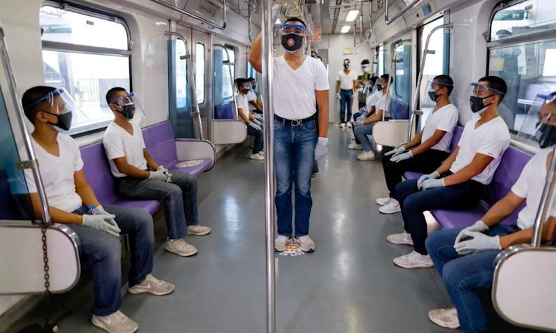 Manila police trainees maintain social distancing on a train during an exercise in preparation for the resumption of public transport