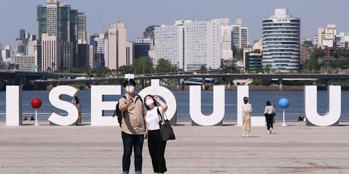 People take selfies at Yeouido Hangang Park in Seoul, South Korea, May 6, 2020.