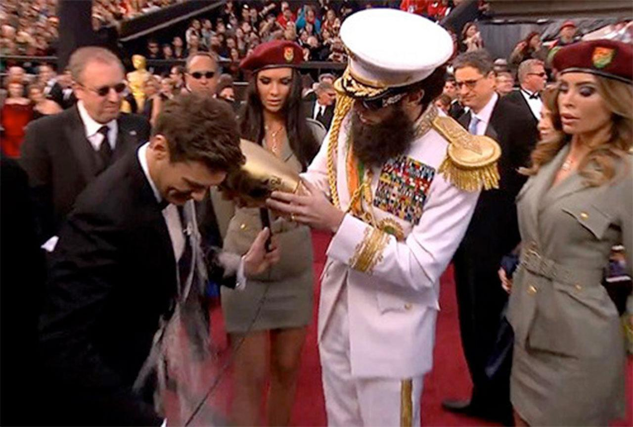 """<p>Done up to the nines in his full military regalia as dictator Admiral General Aladeen, Sacha Baron Cohen approached a wary Ryan Seacrest on the Oscar red carpet, the most hallowed carpet in the world, carrying a suspicious-looking urn. In it was the """"ashes of his tennis doubles partner"""" Kim Jong-il, the late leader of North Korea. Mr. Seacrest slapped on a fake smile when it was emptied on him, but you could tell he wasn't best pleased at having his tuxedo ruined. <i>(Credit: E!)</i></p>"""