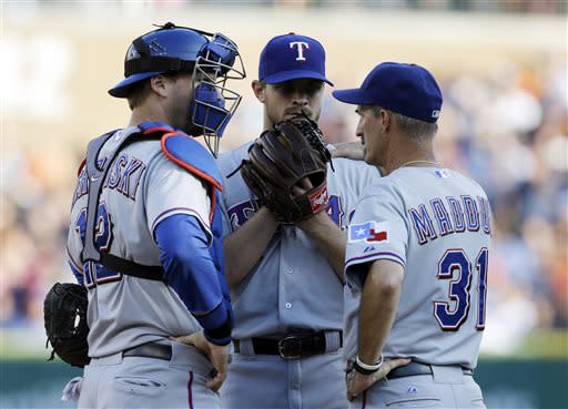 Texas Rangers catcher A.J. Pierzynski (12) and pitching coach Mike Maddux (31) talk with starting pitcher Justin Grimm during the first inning of a baseball game against the Detroit Tigers in Detroit, Friday, July 12, 2013. (AP Photo/Carlos Osorio)