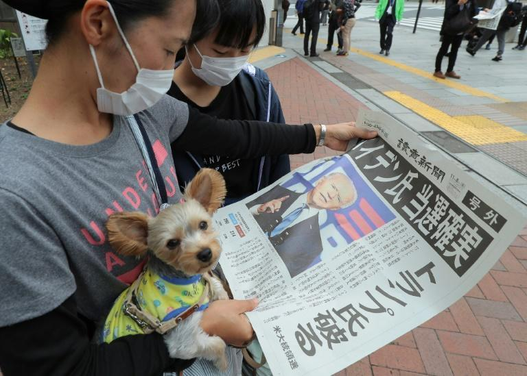 People read an extra edition of a newspaper in Tokyo