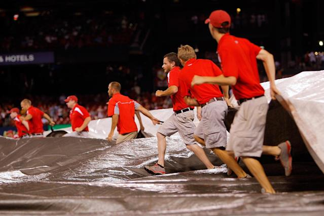Members of the St. Louis Cardinals grounds crew cover the field during a rain delay at the end of the seventh inning of the Cardinals' baseball game against the Cincinnati Reds on Wednesday, Aug. 20, 2014, in St. Louis. (AP Photo/Scott Kane)