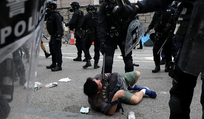 A police officer restrains a protester during clashes outside the Legislative Council Complex. Photo: K.Y. Cheng