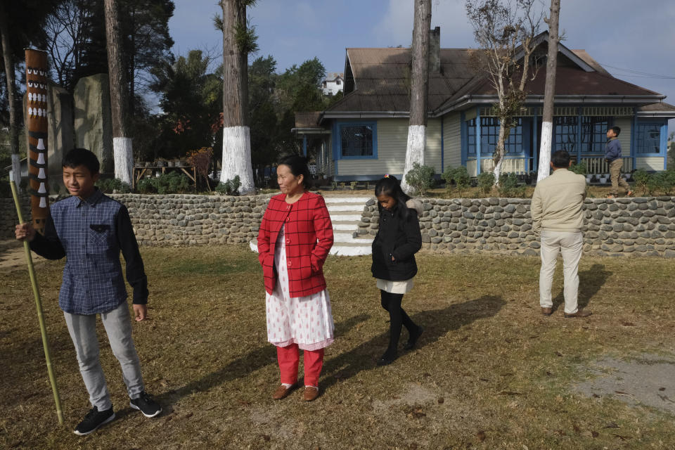 Nurse Shimray Wungreichon, 43, second left, stands in the lawn of the campus where her family lives, along with her husband and three children, a few hours before being administered the COVID-19 vaccine in Ukhrul, in the northeastern Indian state of Manipur, Saturday, Jan. 16, 2021. For the first three months after the pandemic arrived in her region, she couldn't hug her three children, fearing she could potentially pass the virus to them. Her aged parents were to spend all of 2020 living with her, but it was too risky to live with a nurse so they moved back to their distant home village. And her anxiety spiked with every coronavirus test she conducted. (AP Photo/Yirmiyan Arthur)