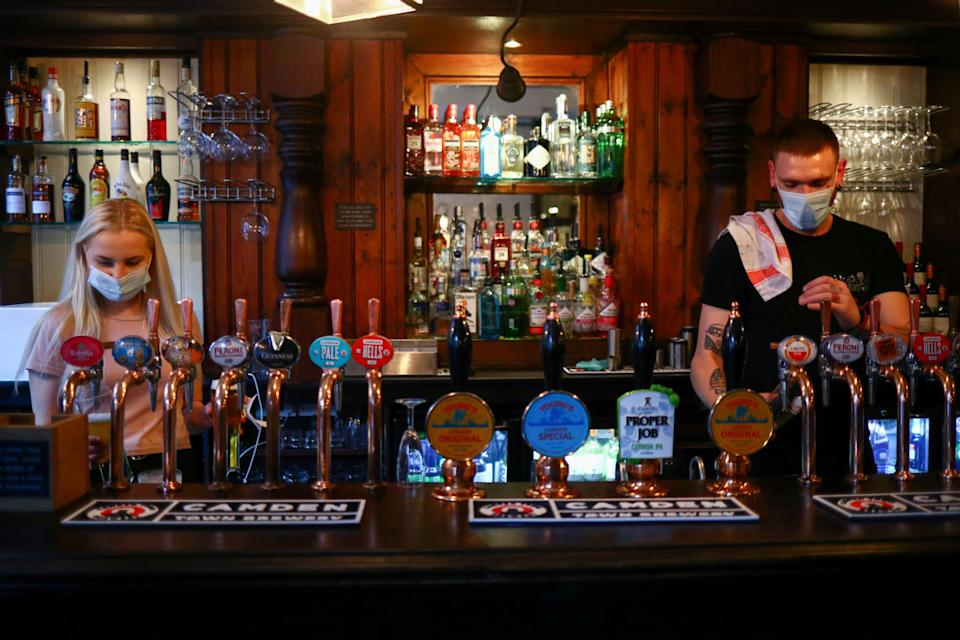 Staff pour drinks at a pub in London Bridge on 24 September, 2020, the day the 10pm curfew was introduced. (REUTERS)