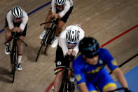 Members of the German and Ukraine men's track cycling team round the track during a training session inside the Izu velodrome at the 2020 Summer Olympics, Thursday, July 29, 2021, in Tokyo, Japan. (AP Photo/Christophe Ena)