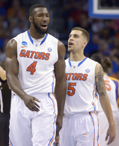 Florida guard Scottie Wilbekin (5) and center Patric Young (4) talk on the court during the second half in a second-round game against Albany in the NCAA college basketball tournament against Albany, Thursday, March 20, 2014, in Orlando, Fla. (AP Photo/Phelan M. Ebenhack)