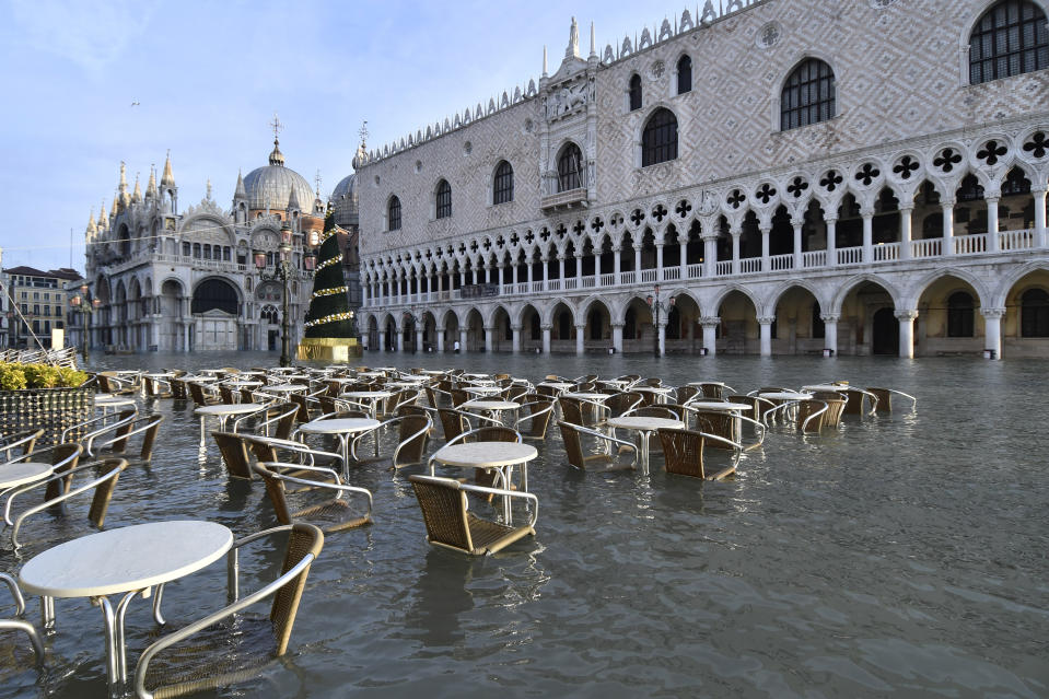 Cafè tables and chairs are partially covered in water during a high tide of 4.72 feet in St Mark's Square, Venice, on Monday. (AP)
