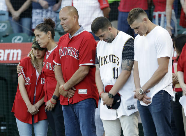 CORRECTS MOTHER'S LAST NAME TO HETMAN, INSTEAD OF SKAGGS - CORRECTS NAME OF PERSON AT MIDDLE - Members of Tyler Skaggs' family, including wife, Carli, left; mother, Debbie Hetman, second from left; and Danny Hetman, third from left, join in a moment of silence in Tyler's honor before the Los Angeles Angels' baseball game against the Seattle Mariners on Friday, July 12, 2019, in Anaheim, Calif. (AP Photo/Marcio Jose Sanchez)