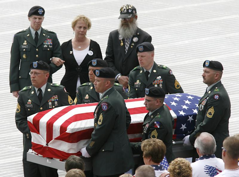 FILE - In this April 27, 2008 file photo, Lt. General James Campbell (Ret.), left, stands with Carolyn and Keith Maupin, as the casket of their son, U.S. Army Staff Sgt. Matt Maupin, is carried to a hearse during a memorial service at Great American Ball Park in Cincinnati. A man in Iraqi custody has confessed to killing Maupin, whose remains were found in 2008, four years after he was kidnapped by insurgents. (AP Photo/David Kohl, File)