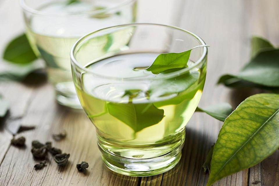 """Swapping just one cup of coffee a day for some green tea can yield major health benefits over time. According to a 2011 meta-analysis published in <em>Obesity Reviews</em>, when consumed together, catechins and caffeine—a combination found in green tea—significantly <a href=""""https://pubmed.ncbi.nlm.nih.gov/21366839/"""" rel=""""nofollow noopener"""" target=""""_blank"""" data-ylk=""""slk:increased study subjects' energy expenditure"""" class=""""link rapid-noclick-resp"""">increased study subjects' energy expenditure</a> and fat burning over a 24-hour period."""
