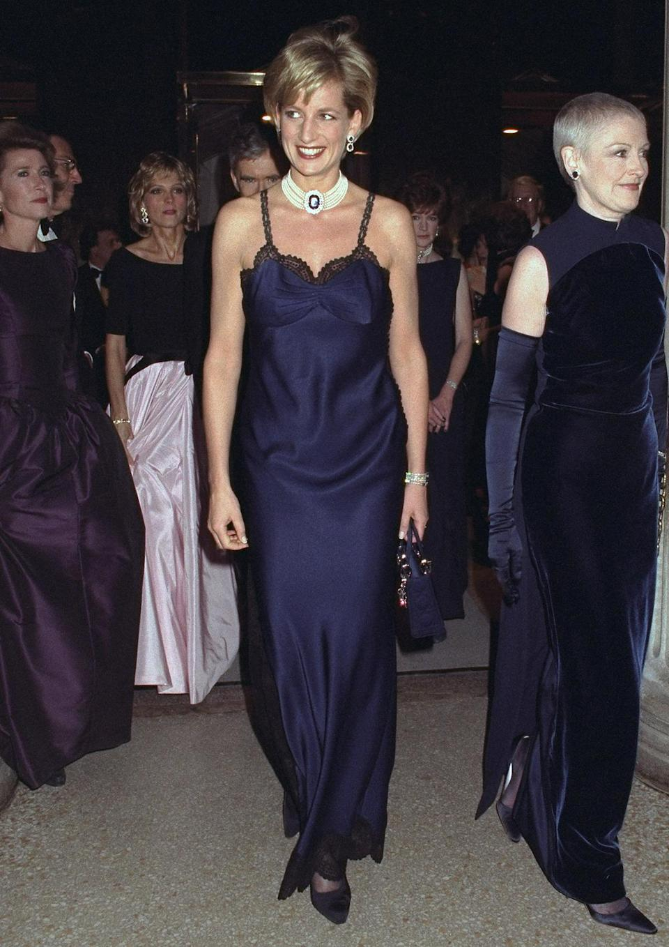 <p>Following her divorce from Prince Charles, Diana once again traveled to N.Y.C., attending the Costume Institute Gala — now known as the Met Gala — in 1996, wearing a navy slip dress. </p>