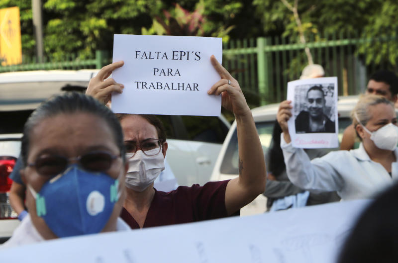 """A health professional holds up the Portuguese phrase: """"Personal protective equipment is lacking for professionals"""" during a protest outside """"Pronto Socorro 28 de Agosto"""" Hospital, in Manaus, Brazil, Monday, April 27, 2020. Cases of the new coronavirus are overwhelming hospitals, morgues and cemeteries across Brazil as Latin America's largest nation veers closer to becoming one of the world's pandemic hot spots. (AP Photo/Edmar Barros)"""