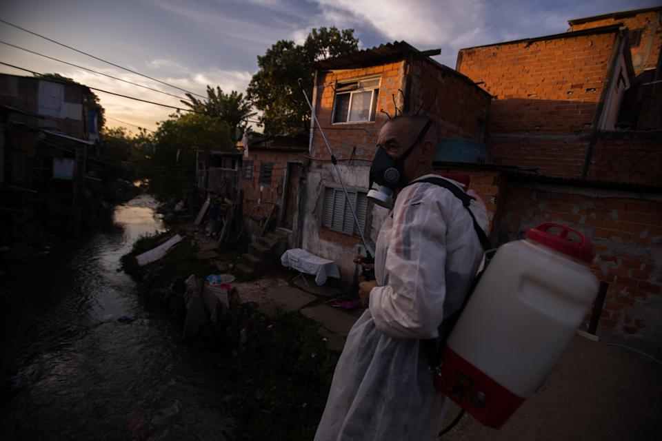 """09 July 2020, Brazil, São Paulo: A member of the neighborhood association """"Amigos da Molecada"""" is standing by a stream that flows through the favela Vietnam in the south of Sao Paulo while participating in a disinfection campaign. Brazil has confirmed 1 755 779 cases of corona. Photo: Andre Lucas/dpa (Photo by Andre Lucas/picture alliance via Getty Images)"""
