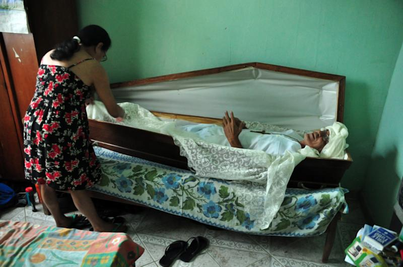 Zeli Ferreira Rosse, 61, and his wife Cleusa Pereira Rosse, reenact how Rosse sleeps in a coffin in Minas Gerais, Brazil, Wednesday Aug. 17, 2011.  Rossi says he sleeps in the coffin on Fridays to honor a friend who died in 1988. The two had agreed to buy the coffin of whoever died first. He says that in 1983 he was seriously hurt in a car accident and his friend, who thought he had died, paid for his coffin. Rossi recovered and when his friend died in 1988 of multiple stab wounds he started sleeping in the coffin to honor his memory.  (AP Photo/Leonardo Morais-Agencia O Globo)  BRAZIL OUT - NAO PUBLICAR NO BRASIL