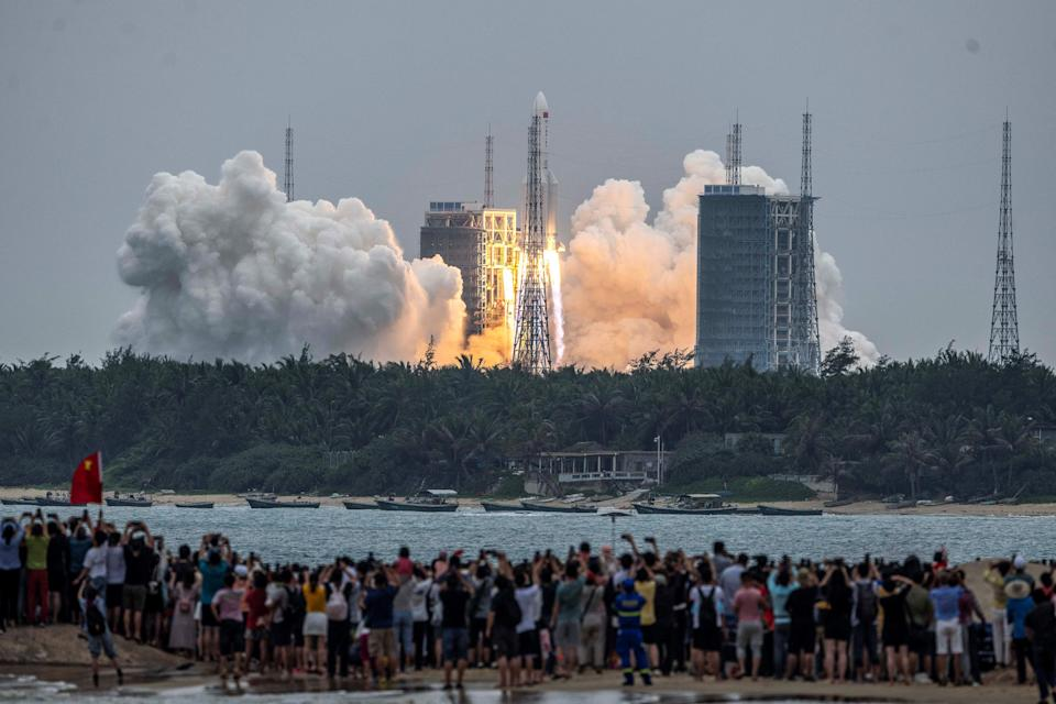 People watch a Long March 5B rocket, carrying China's Tianhe space station core module, as it lifts off.