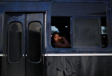A migrant part of a caravan of thousands from Central America trying to reach the United States arrives on a bus to a new temporary shelter in Tijuana Mexico
