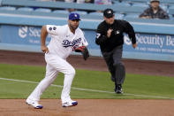 Los Angeles Dodgers first baseman Albert Pujols, left, runs to cover first as Arizona Diamondbacks' Josh Rojas hits a single while first base umpire Dan Merzel watches during the first inning of a baseball game Monday, May 17, 2021, in Los Angeles. (AP Photo/Mark J. Terrill)
