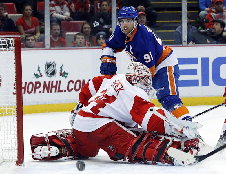 New York Islanders center John Tavares (91) shoots on Detroit Red Wings goalie Petr Mrazek (34), of the Czech Republic, in the first period of an NHL hockey game, Monday, Dec. 23, 2013, in Detroit. (AP Photo/Paul Sancya)