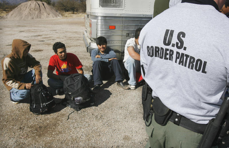FILE - In this Jan. 19, 2007, file photo, Border Patrol agents processes a number of illegal immigrants caught entering the United States, in Sasabe, Arizona. Arizona is still widely viewed in Mexico as the most anti-Mexico state in the U.S., even if the tough anti-migrant law behind that perception has been largely voided. But Arizona's leaders are logging lots of miles to put a new face on their home state. Mexicans are already Arizona's biggest foreign trade partners, with the state exporting $7 billion worth of goods last year, the U.S. Commerce Department says. (AP Photo/Ross D. Franklin, File)