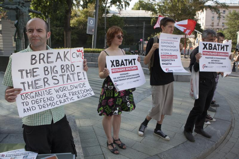 Russian supporters of NSA leaker Edward Snowden rally with posters protesting total surveillance in Moscow, Russia, Friday, July 12, 2013. National Security Agency leaker Edward Snowden wants asylum in Russia and is willing to stop sharing information as a trade-off for such a deal, according to a parliament member who was among a dozen activists and officials to meet with him Friday. (AP Photo/ Alexander Zemlianichenko Jr)