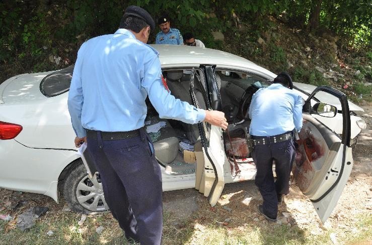 Pakistani police officers examine the car of prosecutor Chaudhry Zulfikar which was targeted by gunmen in Islamabad, Pakistan on Friday, May 3, 2013. Gunmen killed Pakistan's lead prosecutor investigating the assassination of former prime minister Benazir Bhutto as he drove to court in the capital on Friday, throwing the case that also involves former ruler Pervez Musharraf into disarray. (AP Photo/B.K. Bangash)