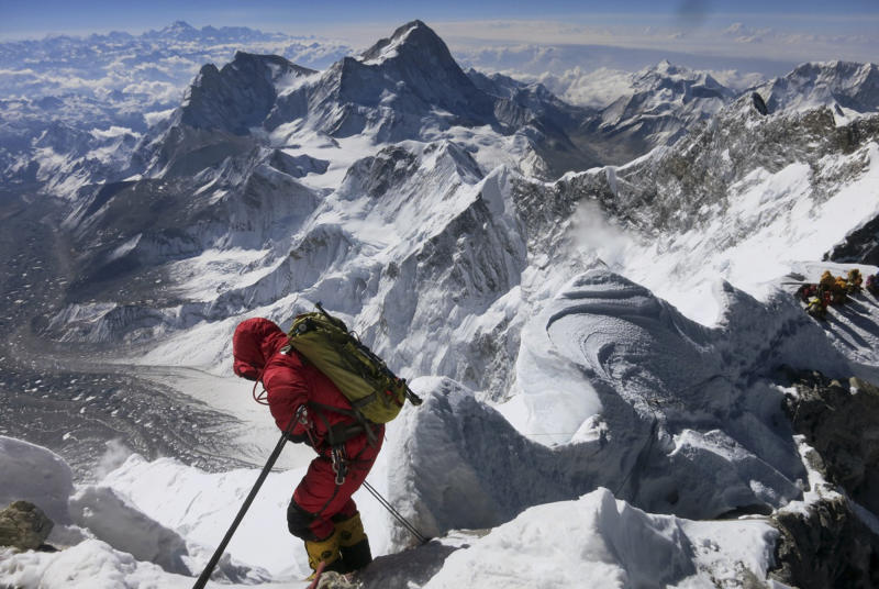 FILE - In this May 18, 2013 file photo released by Alpenglow Expeditions, a climber prepares to descend the Hillary Step as he makes his way down from the summit of Mount Everest, in the Khumbu region of the Nepal Himalayas. Nepal will slash the climbing fees for Mount Everest to attract more mountaineers to the world's highest peak, even as concerns grow about the environmental effects of thousands of climbers who already crowd the mountain during the high season. Madhusudan Burlakoti, head of Nepal's Department of Mountains, said Friday, Feb. 14, 2014 that beginning next year, it will cost $11,000 per climber to climb Everest. (AP Photo/Alpenglow Expeditions, Adrian Ballinger, File) MANDATORY CREDIT, EDITORIAL USE ONLY