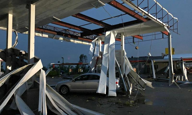 A car is trapped under the fallen metal roof of the Break Time gas station and convenience store in Jefferson City, Missouri.