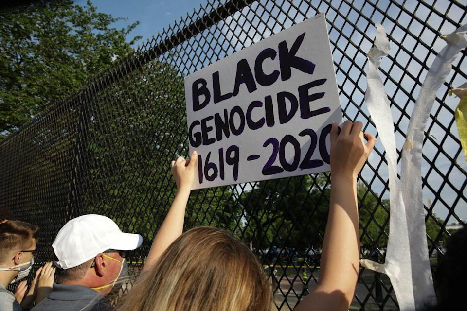 <p>Outside the White House, someone holds a sign that speaks to the long, long history of entrenched racism in the U.S. </p>